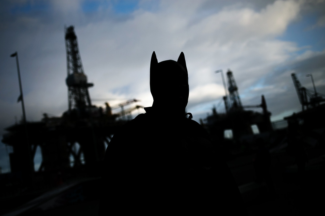 A reveller walks in the street during the day light carnival of Santa Cruz de Tenerife, in the background two oil rigs docked in the port, Canary islands, Spain, Carnival, Saturday, February 21, 2015  (Andrés Gutiérrez/The Stand)