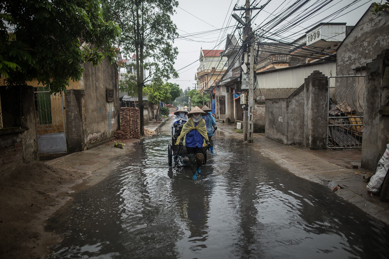 Nguyen Thi Que, Nguyen Thi Dua y Ngo Thi Thuy recorren las calles bajo la lluvia tirando de una carreta llena de piedras de carbón para abastecer a las factorías del poblado de Dai Bai. (Andrés Gutiérrez/El País - Planeta Futuro)
