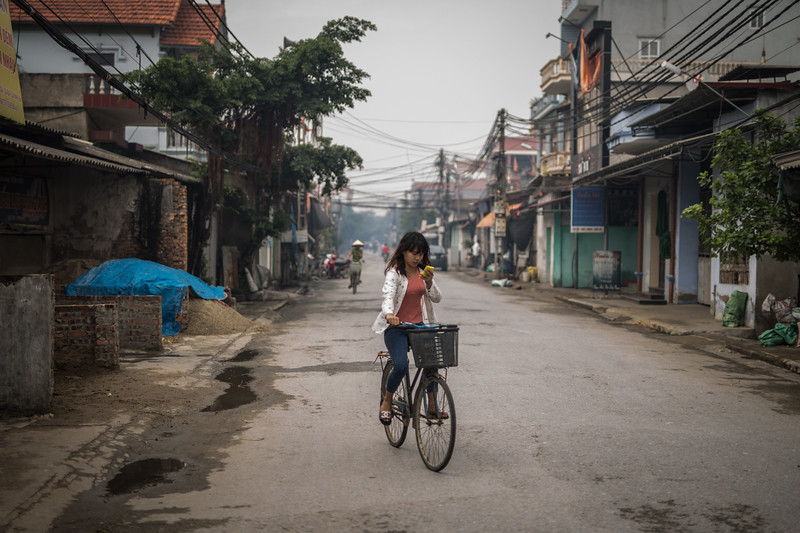 En las calles, los vecinos van y vienen en bicicletas o motociclos, como es común en el país. Se combinan el repique de mazas y martillos sobre carbón o metal y el humo de las factorías para crear un ambiente singular. (Andrés Gutiérrez/El País - Planeta Futuro)