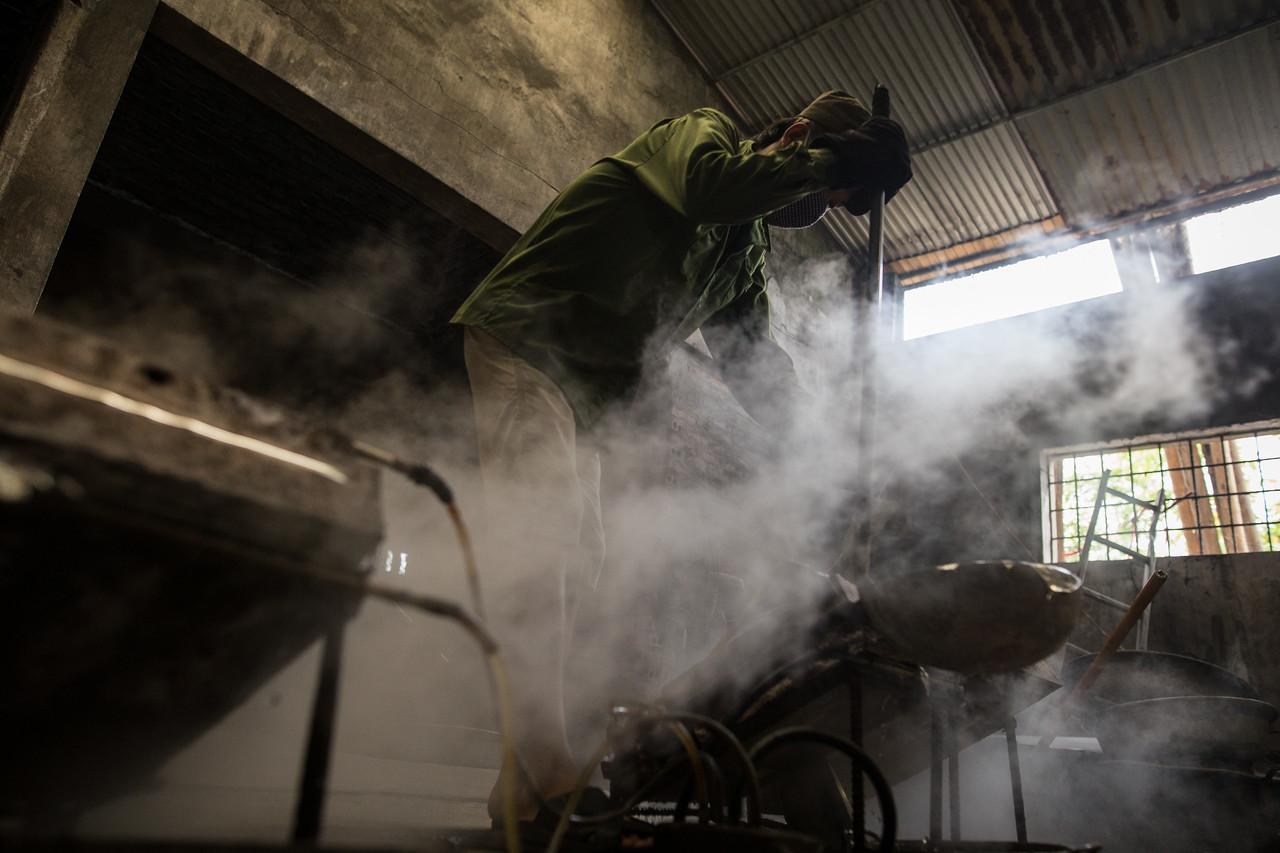 Nguyen Van Thai vierte el aluminio fundido en unos moldes con la ayuda de un cucharón. En unos cinco minutos, las placas de metal se habrán solidificado. Entonces Van Thai las colocará en el suelo para enfriarlas al aire y luego apilarlas en un rincón del taller. (Andrés Gutiérrez/El País - Planeta Futuro)