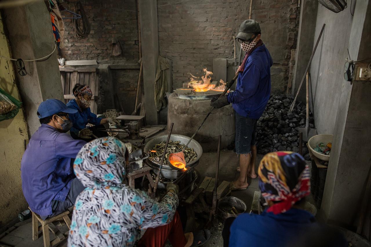 Un grupo de trabajadores de la empresa de Kien dan forma a las tuercas y tornillos que su jefe vende a industrias de maquinaria. Trabajan en la planta baja de la casa donde se encuentra el horno, los moldes, los tornos y un par de ventiladores para disipar el humo. Los trabajadores son vecinos del poblado y afirman que su necesidad es mucho mayor que su preocupación por la polución o las posibles enfermedades. (Andrés Gutiérrez/El País - Planeta Futuro)