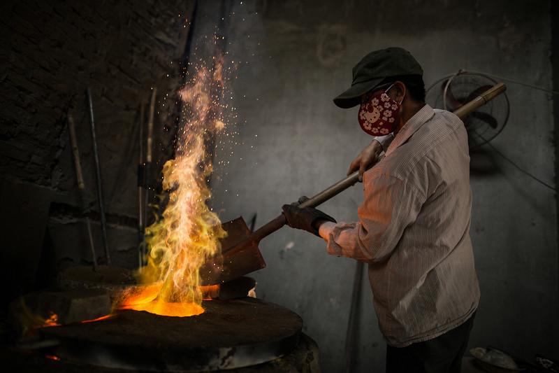 Kien vierte sales en el horno de fundido. Su empresa es familiar aunque su mujer y él contratan a vecinos para aunmentar el rendimiento del negocio. Se dedican a la fabricación y venta de tuercas y tornillos para maquinaria. (Andrés Gutiérrez/El País - Planeta Futuro)