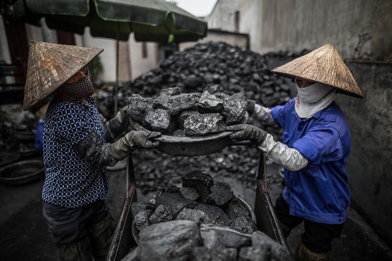 Nguyen Thi Que y Nguyen Thi Dua rompen el carbón en piedras de tamaño similar para luego agruparlas y cargarlas hasta los establecimientos que se las han encargado. Las mujeres superan los cincuenta años de edad y trabajan unas diez horas al día por unos seis euros. (Andrés Gutiérrez/El País - Planeta Futuro)