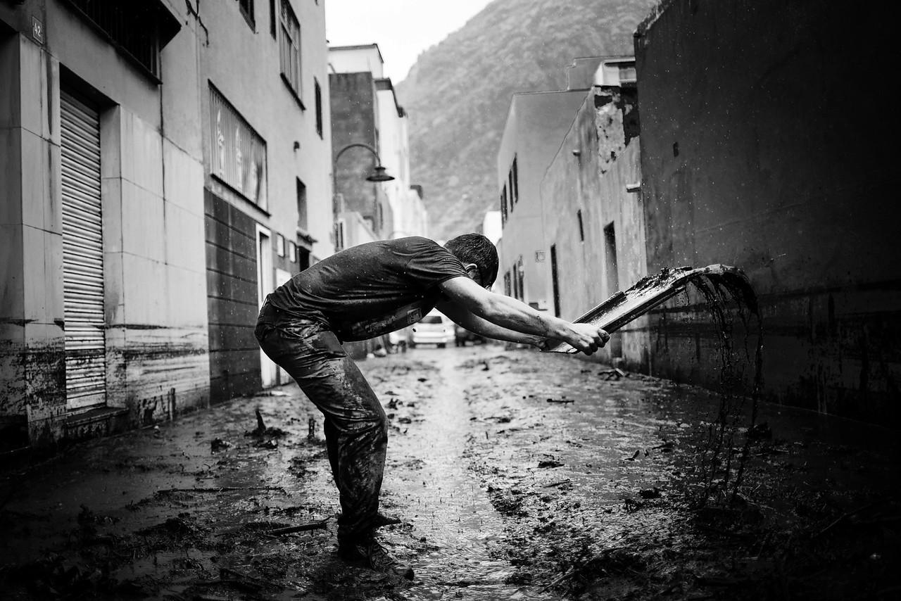 A man helps cleaning the moody street caused by the heavy rain at the coastal neighborhood of San Andres in Santa Cruz de Tenerife, Canary Islands, Spain / AP Andrés Gutiérrez