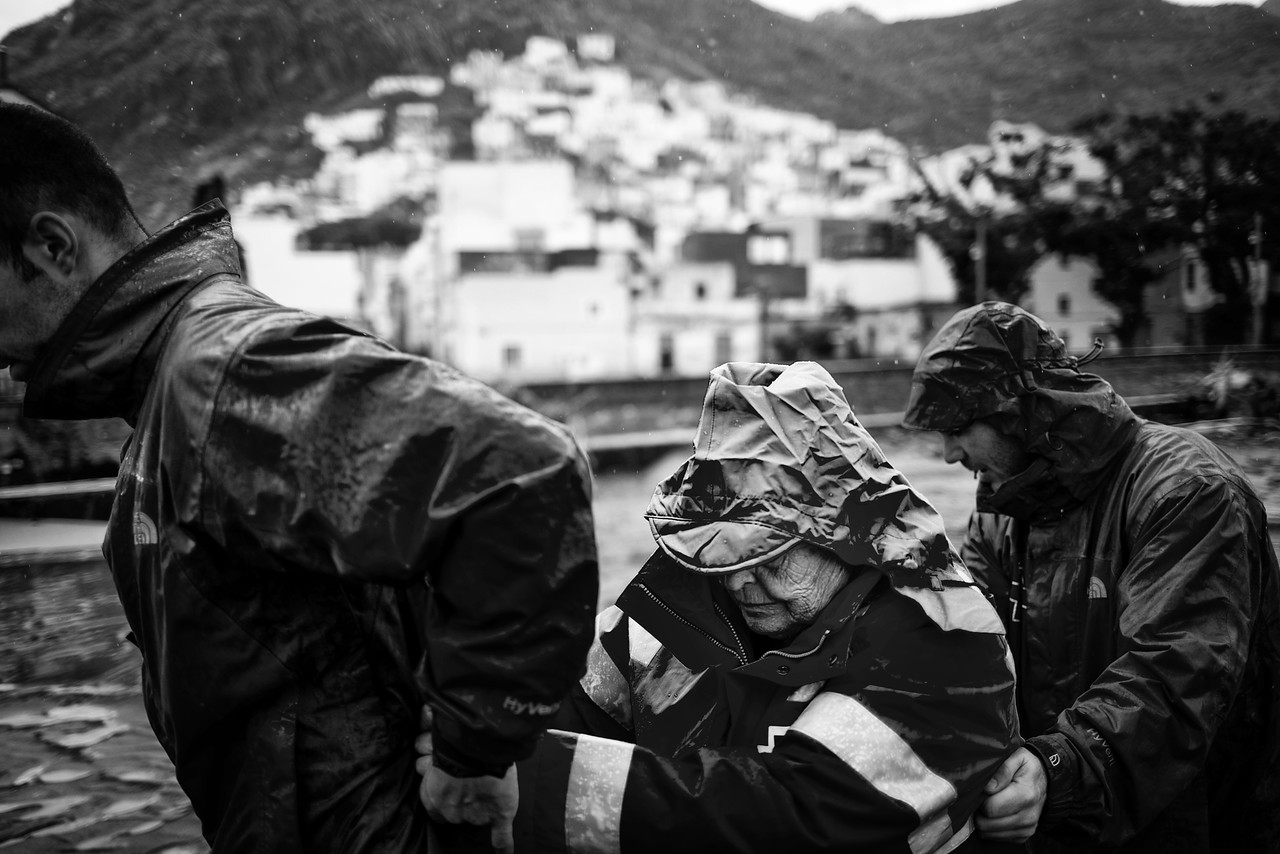Red cross operators help a woman at the coastal neighborhood of San Andres in Santa Cruz de Tenerife, Canary Islands, Spain, Sunday, 19 October, 2014. The heavy rain left more than 130 litres per squared meter in one hour, causing the death of a 56 years old woman, flooding and destruction of several cars and urban furniture