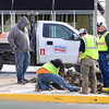Kevin Harvison | Staff photo<br /> McAlester city workers team up to fix a problem on the corner of Third Street and Choctaw Avenue Thursday.