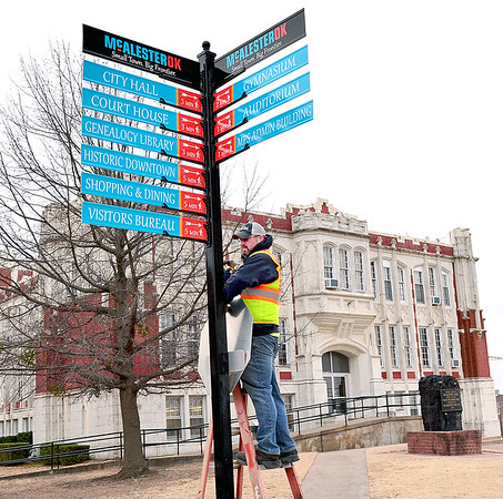 Kevin Harvison | Staff photo<br /> McAlester city worker puts the finishing touches on the new street sign on Washington Avenue and 2nd Street, adding a stop sign Friday morning.