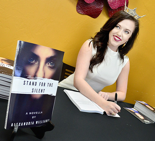 Kevin Harvison | Staff photo<br /> The reigning Miss McAlester and published novelist Alexandria Williams visits as she prepares to sign on of her books at Lucy's Two in McAlester Wednesday.