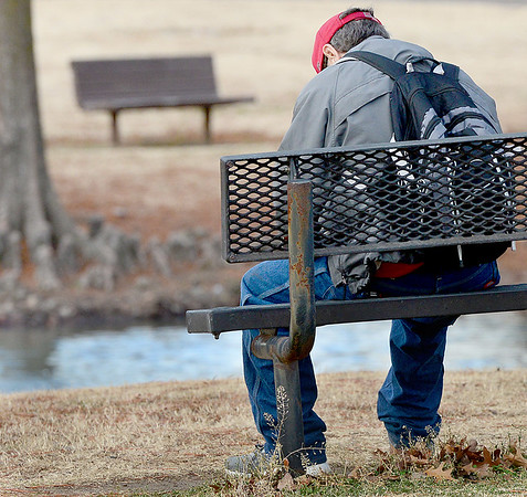 Kevin Harvison | Staff photo<br /> An unidentified man takes advantage of a bench and warm temperatures Thursday morning. Enjoying the outdoors may be limited as cold weather is expected to return throught he week.