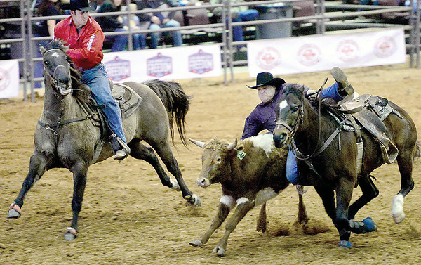 Kevin Harvison | Staff photo<br />  A cowboy gets off his horse attempting to wrestle a steer to the ground during the professional rodeo at the Southeast Expo Saturday.