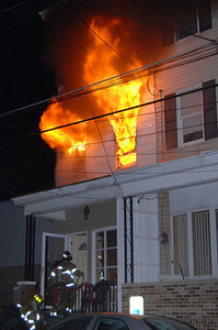 Flames blow from a house on West Spruce Street in Mahanoy City Monday night as firefighters prepare to enter the building.