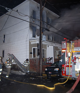 Firefighters put ladders up as smoke pours from a house on West Spruce Street in Mahanoy City Monday night.