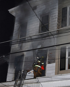 A firefighter enters the second floor window of a home on West Spruce Street in Mahanoy City Monday night.