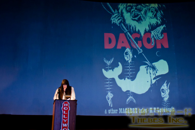 Caitlin Kiernan reads the keynote speech with the cover of her first experience with HPL's writing behind her.