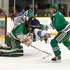 Jeff Dill (2) sails over Whaler goalie Mike Brown (34) in the first period while David Vondracek (3) looks on.