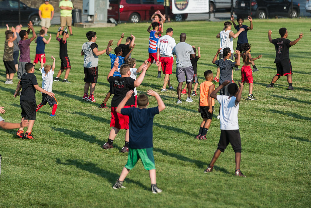 . Kids at the Friday NIght Football Clinic at NIkitas Field start out with some calisthenics. Fitchburg High varsity football coaches and players hosted the free clinic for kids in grades K-12 on Friday, July 21, 2017. SENTINEL&ENTERPRISE/ Jim Marabello