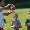 Fitchburg Higfh School head football coach Tom DiGeronimo demomnstfrates a quarterback's proper grip on a football at the Friday NIght Football Clinic at Nikitas Field. Fitchburg High varsity football coaches and players hosted the free clinic for kids in grades K-12 on Friday, July 21, 2017.  SENTINEL&ENTERPRISE/ Jim Marabello