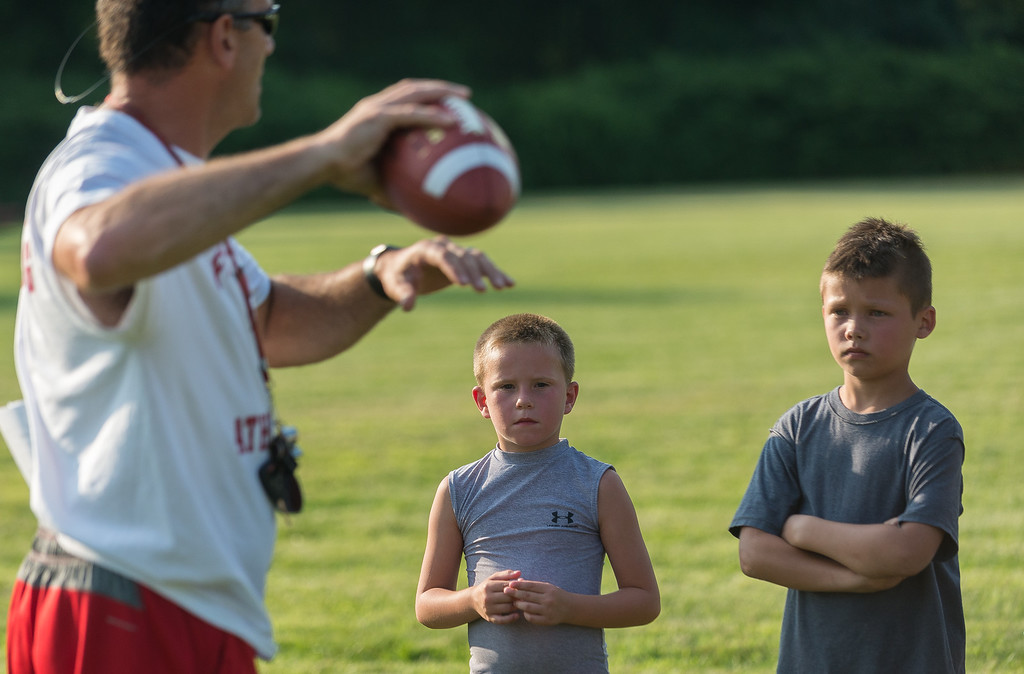 . Fitchburg Higfh School head football coach Tom DiGeronimo demomnstfrates a quarterback\'s proper grip on a football at the Friday NIght Football Clinic at Nikitas Field. Fitchburg High varsity football coaches and players hosted the free clinic for kids in grades K-12 on Friday, July 21, 2017.  SENTINEL&ENTERPRISE/ Jim Marabello