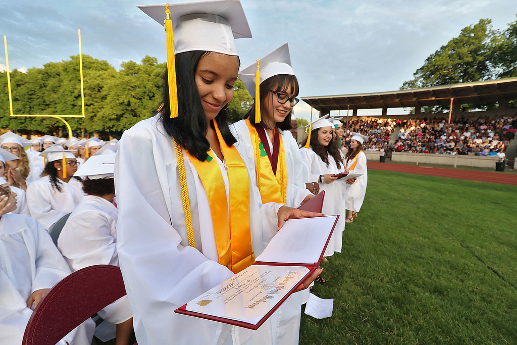 . Fitchburg High School held its 152 commencement exercises on June 1, 2018 at Crocker Field in Fitchburg. Class President Rachely Romero looks over her diploma at the ceremony. SENTINEL & ENTERPRISE/JOHN LOVE