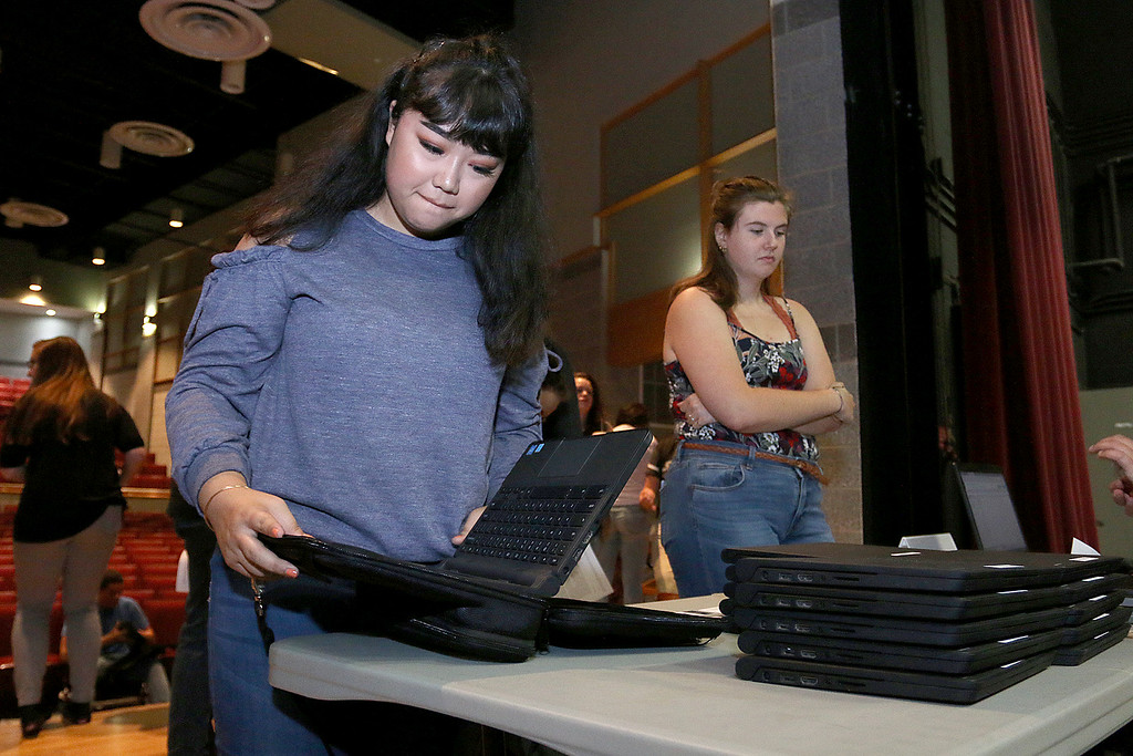 . The junior class at Fitchburg High School got Chromebook laptops on Thursday morning, September 14, 2017. Junior Trinity Figueroa puts her computer into the case while her fellow students stand in line waiting to get theirs. SENTINEL& ENTERPRISE/JOHN LOVE