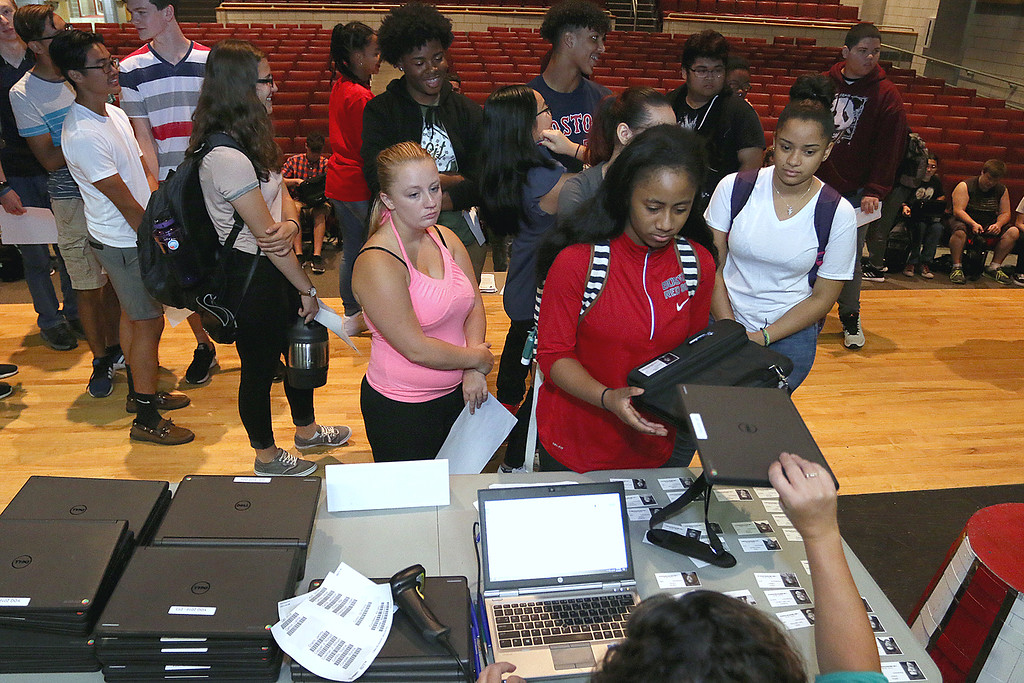 . The junior class at Fitchburg High School got Chromebook laptops on Thursday morning, September 14, 2017. Ashley Demeulle, in pink, and Paola Duarte, in white, wait for their computers as fellow student Leslie Chandler gets hers. SENTINEL& ENTERPRISE/JOHN LOVE