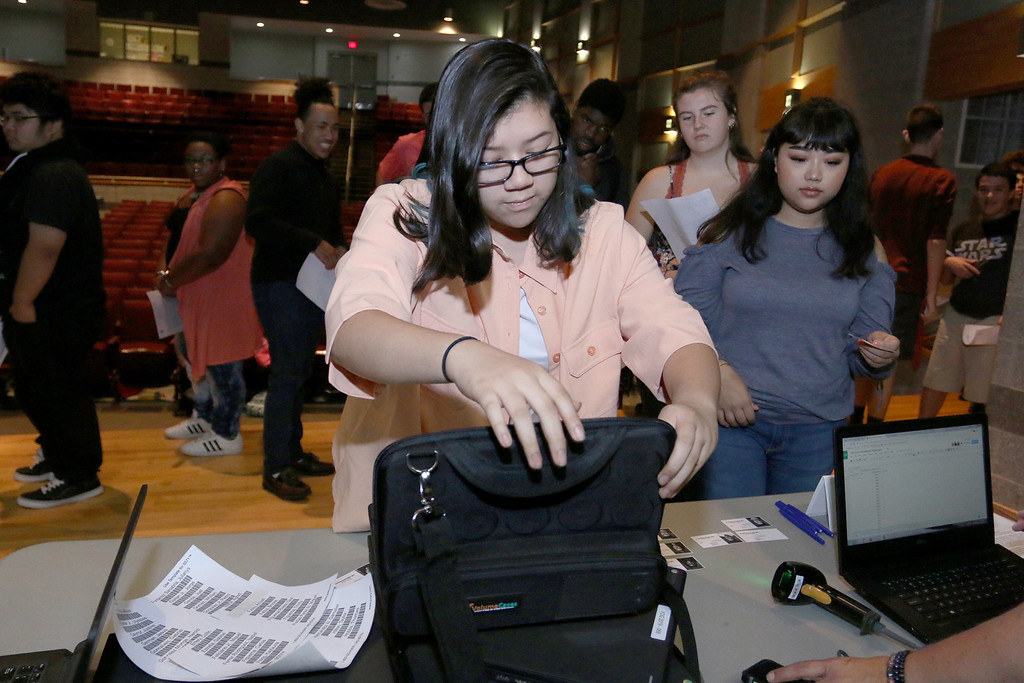 . The junior class at Fitchburg High School got Chromebook laptops on Thursday morning, September 14, 2017. Junior Christina Estrada Aquino puts her computer into the case while her fellow students stand in line waiting to get theirs. SENTINEL& ENTERPRISE/JOHN LOVE