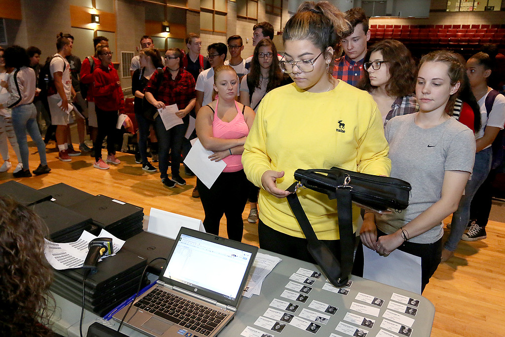 . The junior class at Fitchburg High School got Chromebook laptops on Thursday morning, September 14, 2017. Junior Gabrielle Correa gets her computer as fellow student Alexis Dimond waits just behind her for hers. SENTINEL& ENTERPRISE/JOHN LOVE