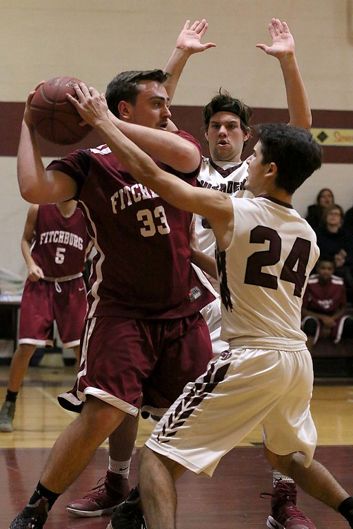 . Groton Dunstable Regional High School player jared LeClerc covers Fitchburg High School player Austin Chandler after got a rebound and was looking for an open teammate to pass to at Tuesday nights game. SENTINEL & ENTERPRISE/JOHN LOVE
