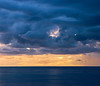 Dramatic clouds over ocean at sunset.