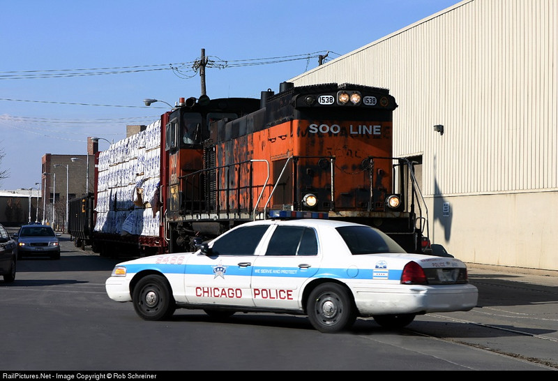 A street running train holds short of the intersection as a CPD squad passes.