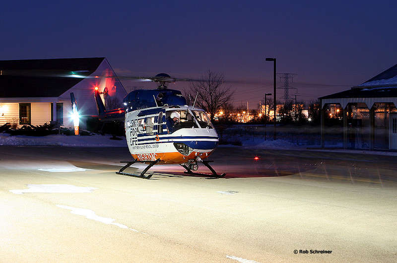 Flight for Life helicopter sits in a parking lot as the crew walks along the right side of the picture taking a paitent to the rear.