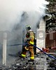 Just before noon today, the McHenry township Fire Protection District was dispatched to the 3900 block of Pitzen Road in Johnsburg for a report of a structure fire with people trapped. While responding, the 911 Operator advised that the Johnsburg Police were on the scene confirming a 'working fire' and that the ccupants were out of the house.On arrival, there was fire showing from the first floor of a large 2-story, single family dwelling. The house was set in a valley about 150' off the roadway, adjacent to Pistakee Bay. This response area does not have fire hydrants, so water had to be drafted from the bay near Bald Knob marina. Initially, an aggressive fire attack took place on the interior of the building, but the strategy was changed when conditions rapidly deteriorated. Crews were forced to retreat from the inside and attack the fire from the exterior. Because of the construction features of the building, fire raced from the basement though the exterior walls into the attic.