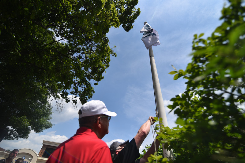 Race officials alongside city officials raise the Olympic flag in the center of the 2018 Longsjo Classic in Fitchburg on Sunday.  SENTINEL & ENTERPRiSE JEFF PORTER