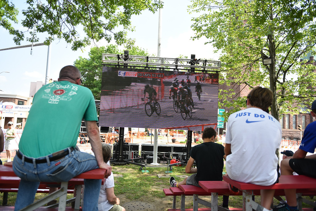 . Spectators escape the heat by watching the race in the shade on the big screen during the 2018 Longsjo Classic in Fitchburg on Sunday.  SENTINEL & ENTERPRiSE JEFF PORTER