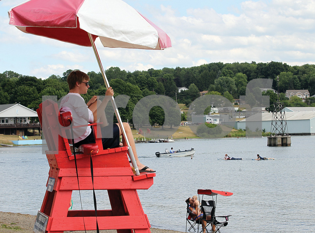 Spencer Tulis/Finger Lakes Times<br /> Nate Christensen, 20 of Penn Yan sits atop his lifeguard's chair at Indian Pines Park in Penn Yan. The exceptionally warm weather is drawing many to the cool waters of area lakes like this one- Keuka Lake.