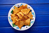 Nachos chips on mexican plate over blue