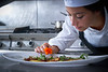 Chef woman garnishing flower in dish at kitchen