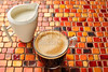 Coffee glass cup with cream on tiles red table