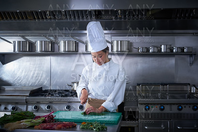 Chef woman portrait cutting at kitchen