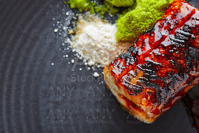Grilled smoked eel on black plate