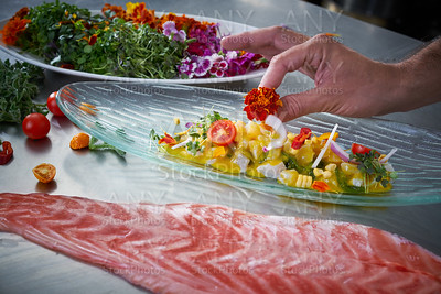 Chef hands garnishing flower in ceviche dish