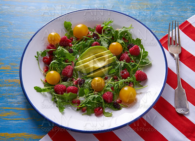Avocado and berries salad with arugula and tomato