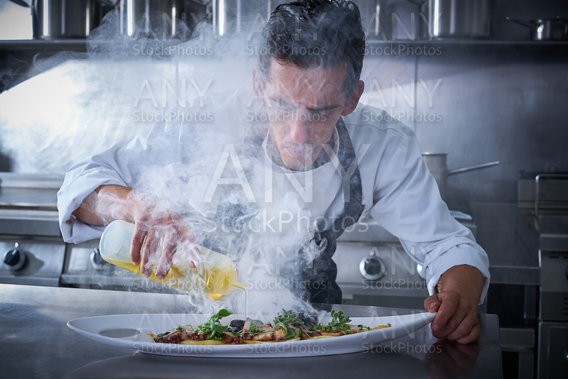 Chef working in kitchen with smoke and oil