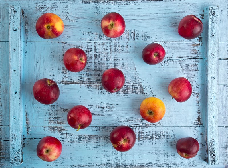 red apples which are neither dyed blue rustic wooden table