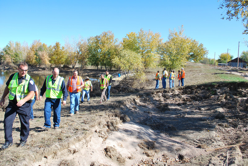 Interim Police Chief Darin Sagel and City Manager Jeff Wells hike with other city staff and Fort Morgan City Council members during a tour of Riverside Park Wednesday, Oct. 23, 2013. The large hole shown here used to be the trail, but washed out after the main part of the flood as the water was receding, City Engineer Brad Curtis said. (Jenni Grubbs/Fort Morgan Times)