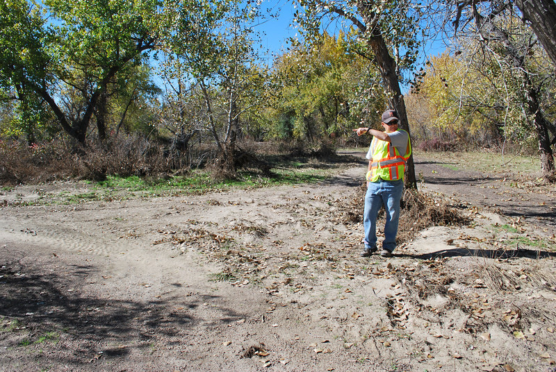 The city will set up barricades at the confluence of trails shown here in Riverside Park to show which part of the park is being reopened Nov. 4 and which areas will still be closed. Parks Superintendent Doak Duke points to the trail that will be opened, while the one running behind and beside him will remain closed. (Jenni Grubbs/Fort Morgan Times)