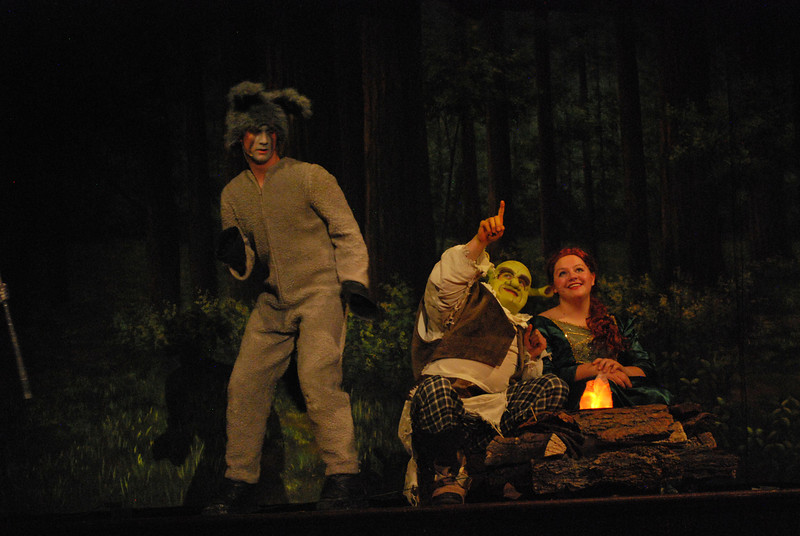 "Shrek (Matthew Hofman) and Princess Fiona (Nancy Hochanadel) share a moment at their campfire as Donkey (Kenny Thompson) tries to get them to realize it during Fort Morgan High School's production of ""Shrek the Musical."" FMHS is only the second Colorado high school to put on the Broadway musical. (Jenni Grubbs/Fort Morgan Times)"