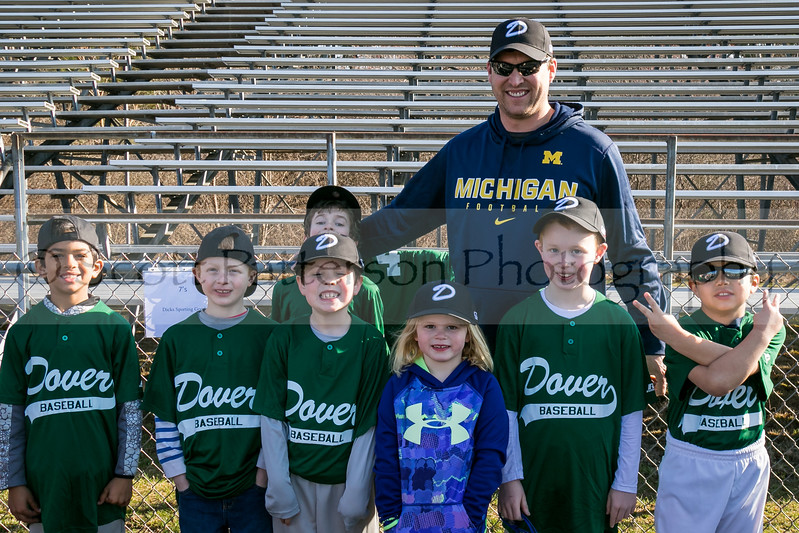 Dover Baseball Coach Kevin Hebert stands with his players Brayden Patel, Brennan Ronchi, Teddy Fuller, Aiden McCann, Ryan Hebert, Emma Hebert and Ben Puertas, left to right, during opening day ceremonies in Dover Saturday. [Scott Patterson/Fosters.com]