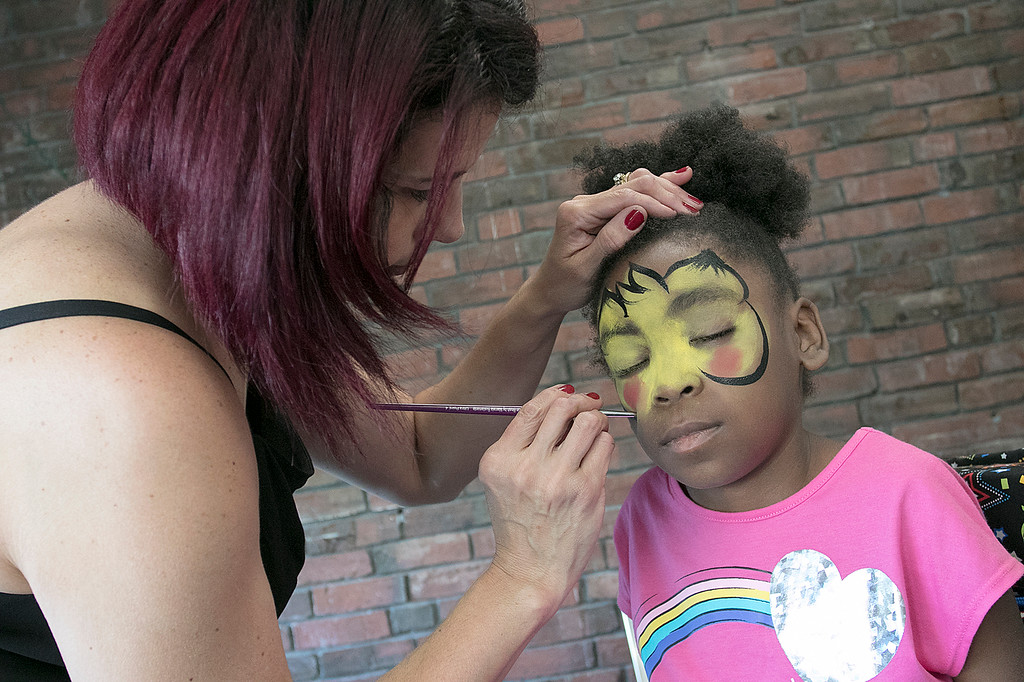 . The Fitchburg Public Library held a summer Reading Kickoff Party on Thursday, June 27, 2019. Getting her face painted like Pikachu by Nicole Kirrane with Face Escapes is J\'Lynn Campbell, 9, from Fitchburg. SENTINEL & ENTERPRISE/JOHN LOVE