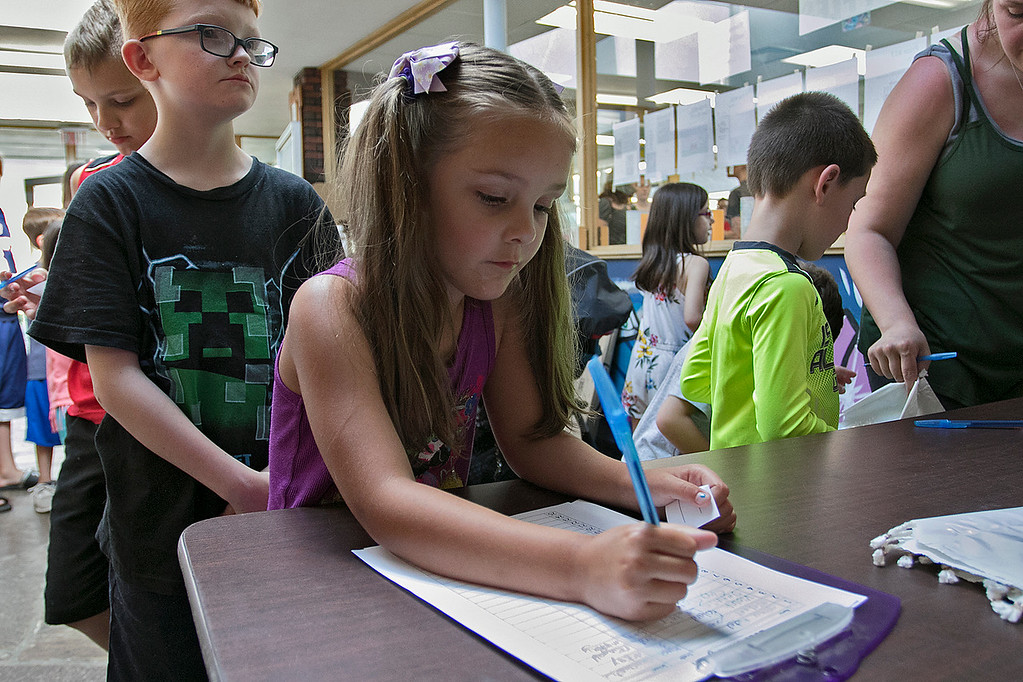 . The Fitchburg Public Library held a summer Reading Kickoff Party on Thursday, June 27, 2019. Charlotte LaClaire, a first grade student at the McKay Arts Academy signs up for the summer reading program during their kickoff. SENTINEL & ENTERPRISE/JOHN LOVE